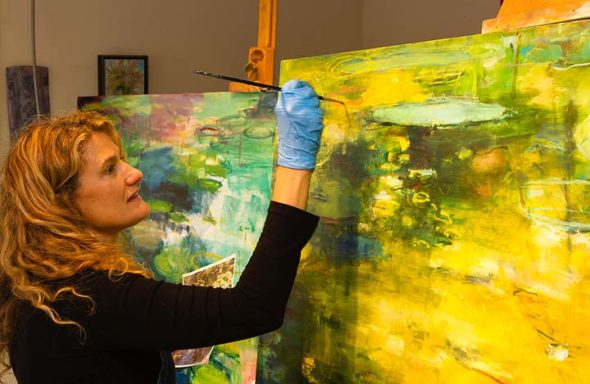 "A solo show by local artist Jennifer Rosengarten is opening at the Springfield Museum of Art this Saturday, April 22, with a reception from 5:30 to 7 p.m. ""Jennifer Rosengarten: Gardens & Ponds"" will run through Jan. 7, 2018. Pictured here in her Dayton Street studio, the artist is increasingly well-known for her evocative paintings of the natural world. (Submitted photo by Bill Franz)"
