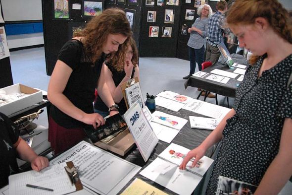 "Students Ellery Bledsoe, Greta Kremer and Aza Hurwitz peruse as PBL project, ""Flipping Stereotypes: A Mix-and-Match Book of the American Teenager."" at the McKinney/YSHS PBL Exhibition Night on Wednesday, May 10. (Photos by Matt Minde)"