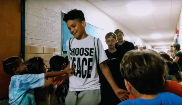"Sixth-graders give low-fives to Kindergarteners at the annual sixth-grade ""clap-out."""