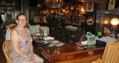 Christine Monroe-Beard, who purchased Ye Olde Trail Tavern in January with her husband, Don Beard, recently sat at the restaurant's bar surrounded by photographs of old documents and newspaper clippings about the Tavern's 190-year history. The couple has been rehabilitating the historic tavern and is hoping to reopen the establishment within the next two weeks. In the meantime, Monroe-Beard has become an expert in the building's series of owners and uses. (Photo by Dylan Taylor-Lehman)