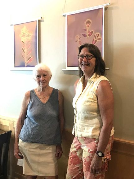 "Photographer Dennie Eagleson, a volunteer with Tecumseh Land Trust (left), and TLT Executive Director Krista Magaw recently posed by two of Eagleson's lumen prints on display in ""The Pollinator Show"" at The Winds Café through August. A public reception will be Sunday, July 16, 5–7 p.m. (Photo by Carol Simmons)"