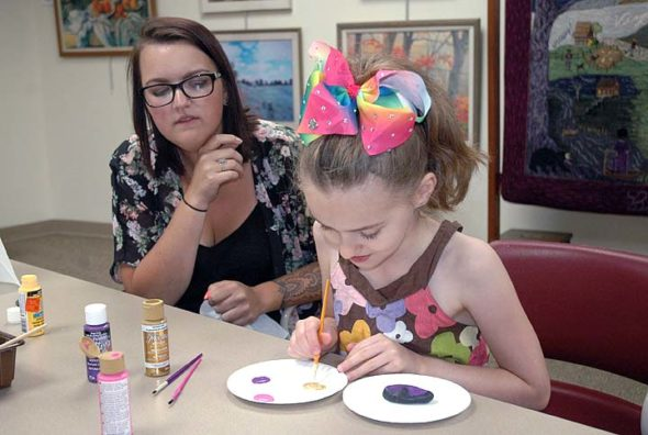 Brooke Rodgers, 7, of Yellow Springs, paints a kindness rock at YS Library, under the guidance of Elizabeth Russell, the library's new part-time youth services librarian. (Photo by Carol Simmons)