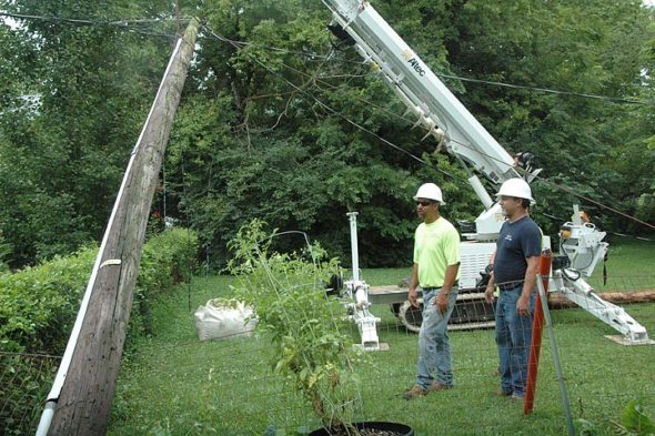 """Johnnie Burns, right, the Village of Yellow Springs superintendent of electric and water distribution, recently received a Larry Hobart """"Seven Hats"""" award from the the American Association of Public Power, a national award honoring managers of small town utilities. Burns is shown here last Friday helping to reset an electric pole on Walnut Street knocked over by a fallen tree. At left is Kent Harding. (Photo by Diane Chiddister)"""