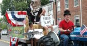"The local effort to erect an ""over-life-size"" bronze statue of Wheeling Gaunt made a splash at the Yellow Springs Fourth of July parade last summer. Project steering committee member Dave Neuhardt, president of the the Yellow Springs Historical Society, is behind the tractor wheel. Visible on board the float, which featured a papier-maché depiction of Gaunt's head, are Malaya Booth and Bob Huston. (Archive photo by Diane Chiddister)"