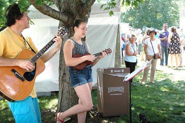 Adding aural aesthetics to the annual Art on the Lawn were buskers — some younger, some older — like Matt Minde and daughter Eliza Minde-Berman, who played the crowds for a good three hours. (Photo by Diane Chiddister)