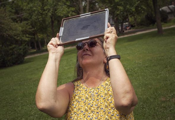 Rebecca Holihan uses a pane of glass covered in candle soot to view the Great Eclipse of 2017 at Gaunt Park. (Photo by Matthew Collins)