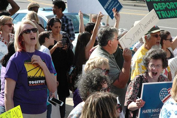 "Yellow Springs resident Susan Alberter (left front), the driving force behind Greene County Indivisible: Awake and Watching, was among a number of group members who participated in a rally Tuesday, Sept. 5, in downtown Dayton to protest the president's efforts to rescind President Barack Obama's executive order known as DACA, or Deferred Action for Childhood Arrivals. An estimated 100 people, many from Yellow Springs, gathered outside U.S. Rep. Mike Turner's regional office to urge Turner to help retain the legal status of 800,000 young people called ""Dreamers."" (Photo by Carol Simmons)"