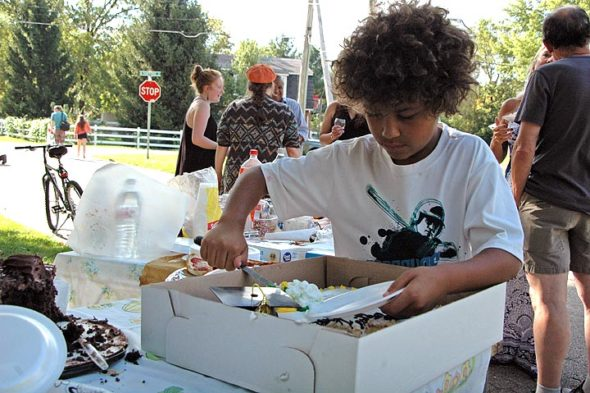 """The North Stafford and Union streets block party not only served as a late-summer gathering, but also as a graduation celebration for Horton, who recently received her master's in mental health counseling. Pictured here, Jayden Toms was one of many block-partiers who cut, with gusto, into the big """"Happy Graduation"""" cake. (Photos by Audrey Hackett)"""