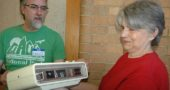 "Deborah Dillon brought her ""chirping"" 46-year-old clock radio to last Saturday's Repair Café, a free event for repairing household items such as clothing, furniture, lamps, computers and other small electronics. Duard Headley, also pictured, was one of the volunteer ""fixers."" The Repair Café was organized by Kat Walter of YS Time Exchange. (Photo by Audrey Hackett)"