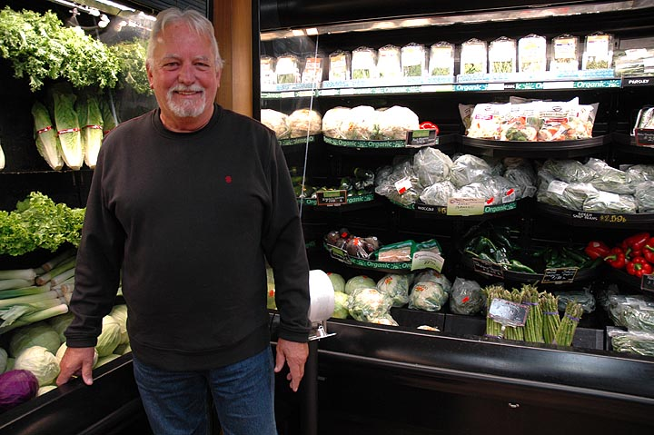 Tom Gray, the owner of Tom's Market, in front of the store's produce department, which was upgraded several years ago. A small independent grocery in competition with the recently built Kroger Marketplace in Fairborn, Tom's Market keeps its focus on responding to customers' needs. (Photo by Diane Chiddister