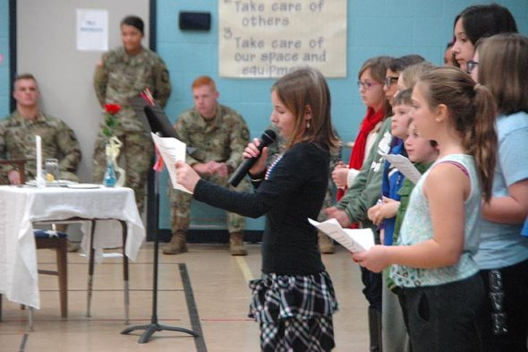 Mills Lawn students honored veterans and current service members Monday, on the observed Veteran's Day, by inviting them to a luncheon. Students gave readings on the history of the holiday, and the 5th- and 6th-grade choir sang the national anthem. The mood was celebratory, yet respectful. The table in the background was set and purposely left empty to remind the assemled of those veterans who had died or were otherwise unable to attend. Above, ????? ????????? reads about Armistice Day, which celebrated the end of World War I, and later became known as Veteran's Day in the United States. (Photo by Matt Minde)