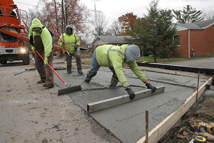 Several workers from Axis Civil Construction in Columbus poured concrete last week for a new sidewalk along the east side of Winter Street, part of the Safe Routes to School project. Shown above, crew leader Jacob Powell smoothed concrete after the pour. The project also includes a new section of sidewalk on Fairfield Pike from Fair Acres to Winter, in an effort to enhance safety for children walking to school. (Photo by Diane Chiddister)