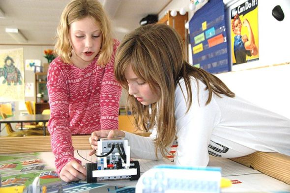 Mills Lawn fourth-graders Malayna Buster, left, and Hannah Parker adjust a robot named Bratwurst, which they helped program as part of their FIRST Lego League after-school team. The girls are members of one of two local 10-member teams that will be competing in a regional tournament Sunday, Dec. 10, being hosted by YS High School junior Alex Ronnebaum at the high school. (photo by Carol Simmons)