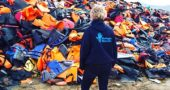 A volunteer for Refugee Rescue on the Greek island of Lesbos, which meets boats full of refugees as they arrive, is shown in front of a huge pile of life jackets used by refugees fleeing their homelands. Villager Regina Brecha, along with Anna Williamson, also of Yellow Springs, are currently among the volunteers. Her mother, Kaethi Seidl, and Beth Holyoke, who have both volunteered at Greek refugee camps, are holding a fundraiser for the cause on Tuesday, Dec. 5, at 7 p.m. at the Yellow Springs Brewery. (Submitted Photo)