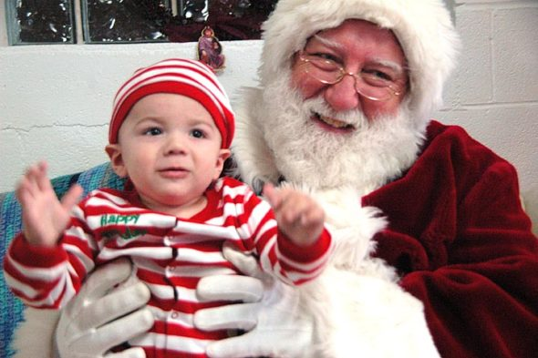 Carter McAllister, great-grandson of villager Patti McAllister, sized up Santa. (photo by Diane Chiddister)