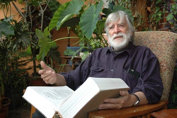 """Local almanac writer Bill Felker recently published a new book, """"Home Is the Prime Meridian,"""" a collection of nature essays drawn from his News columns and elsewhere. Pictured here in his greenhouse with a bound version of his daybook, Felker recalled how his wife's gift of a barometer in 1972 got him started on observing weather patterns and other natural phenomena. (Photo by Audrey Hackett)"""
