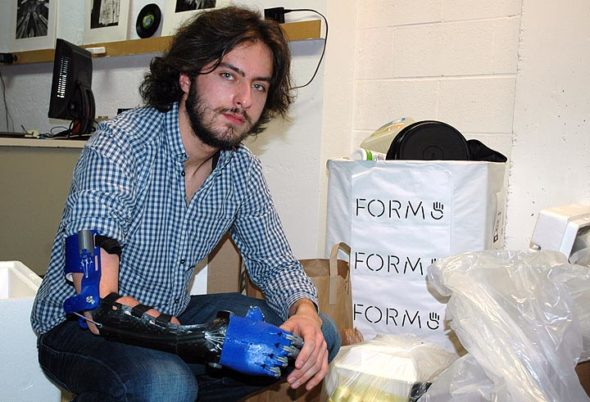 First-year Antioch College student Aaron Westbrook is the founder and CEO of Form5 Prosthetics, a company that makes prosthetic limbs, like the one he's wearing, from recycled plastic. Westbrook is pictured in his lab space at Antioch with some of the plastic he collected from the local community during a recent plastics drive. (Photo by Audrey Hackett)