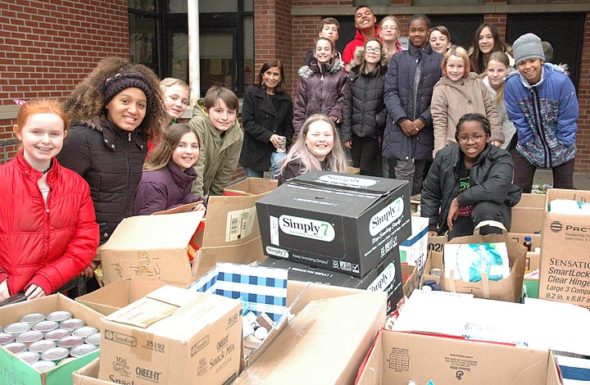 Members of Mills Lawn School Student Council posed after loading onto a flatbed trailer a record haul from this year's record holiday food drive. (Photo by Matt Minde)