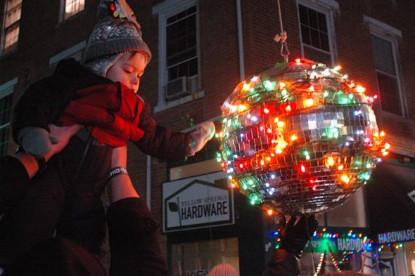 While technically not a baby, 21-month-old Jack Rudegeair, ball-drop-master Lance's grandson, got the opportunity to touch the enchanting New Year's sphere just after midnight, held aloft by his father, Shawn. (Photo by Matt Minde)