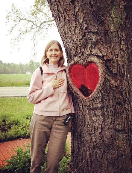 """February is American Heart Month, and many don't know that heart disease is the No. 1 killer of women. Shown above, Lynda Terry of Yellow Springs, who suffered a heart attack in 2011, is shown at a """"heart"""" tree on the bike path after she and her family completed a walk in support of the 1st Annual SCAD Research Walk/Run taking place that day. Terry's heart attack was caused by SCAD, or spontaneous coronary artery dissection, a rare coronary disease that strikes younger women. (Submitted Photo)"""
