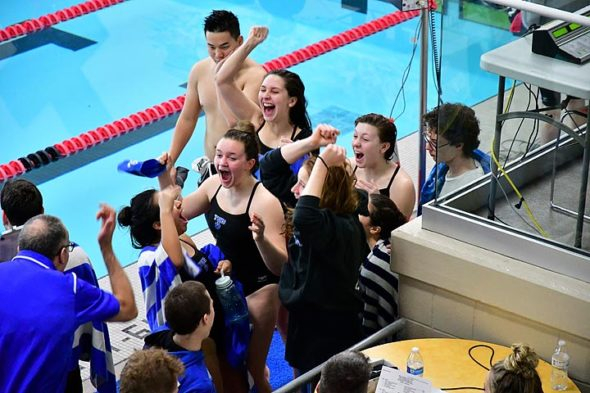 """The Yellow Springs High School girls swim team won the Metro Buckeye Conference championship for the third year in a row on Saturday, Feb. 3. Shown above celebrating are Coach Franklin Halley (lower left) and team members Sara Zendlovitz, Madison Werner, Eden Spriggs, Natalie Galarza, Jude Meekin, Aza Hurwitz and Ellery Bledsoe.  In a statement this week, YSHS Athletic Director Nate Baker wrote, """"We want to extend a huge congratulations to the YS swim team as they earned the 2018 Metro Buckeye Conference title! This caps off a 3-peat as they now have been the conference champs 3 years in a row — what an amazing accomplishment! This team and coaching staff has shown a drive and commitment level that we strive for across the board for our teams.""""  The girls will swim this Friday, Feb. 16, at the districts meet at Miami University. (Submitted photo by Kathleen Galarza)"""