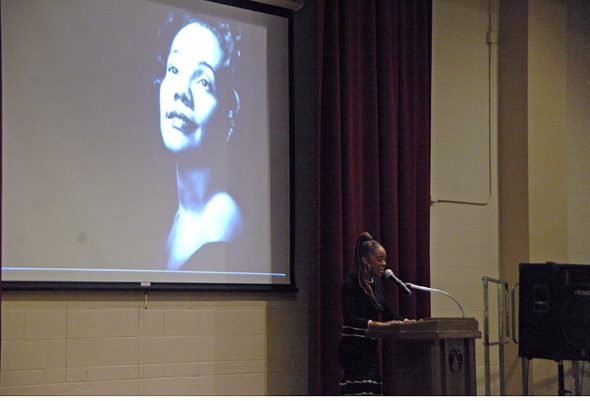 Tamika Mallory, co-president of the Women's March, stands in front of a projected photograph of Coretta Scott King, Antioch alumna. Mallory gave a talk at Antioch College on April 26, the day after she received the second annual Coretta Scott King Legacy Award. She told the audience that the struggle for civil rights continues and that fighting systemic racism is everyone's responsibility. (Photo by Megan Bachman)