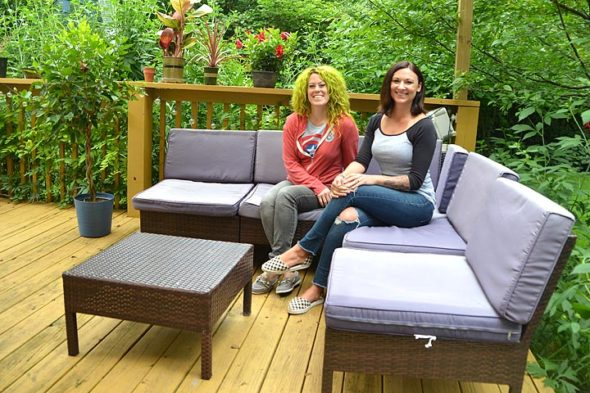 Brittany Baum, left, and Rachel Price, shown here on Baum's backyard deck, are co-organizers of the first Yellow Springs Porchfest, to take place Saturday, Oct. 6, from noon to 7 p.m. At the event, local musicians will play for free on villagers' porches, decks and yards. (Photo by Diane Chiddister)