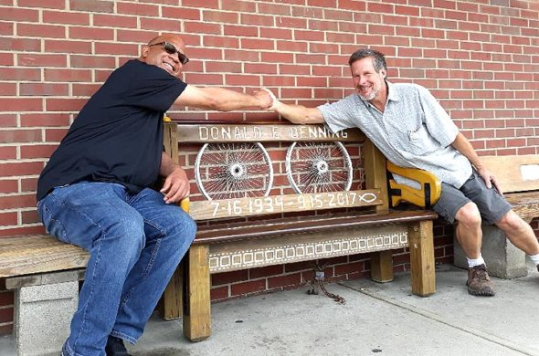 A memorial bench for village resident Don Benning, who died last year, is in place in front of Tom's Market, thanks to the efforts of lifelong family friend Shelly Blackman, left, who commissioned locally based artisan Bruce Parker, right, to create the bench that reflects Benning's multiple interests. (photo by Carol Simmons)