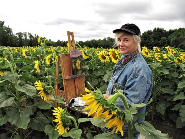 Local artist Christine Klinger is pictured painting in the sunflower field north of town. (submitted photo)