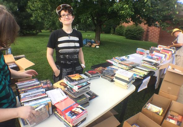 Ember McDonald of Yellow Springs browsed through used books and CDs at the 38th annual YS Book Fair, held last weekend at Mills Lawn. (Photo by Carla Steiger)