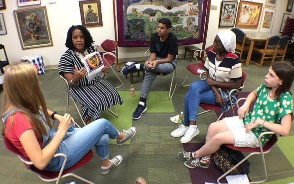 Students Evelyn Potter, Sokhna Mouslt Sene and Delia Halley listen to Aurelia Blake as she gives them background information on black civil rights activist Bayard Rustin at the Yellow Springs Library Monday afternoon. (Photo by Carla Steiger)