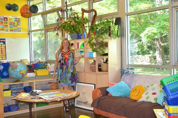 Cathleen Tong, Antioch School's new Younger Group teacher, has taken advantage of the windows lining her classroom to fill the space with light and color. A framed picture of The Wolf sailing ship, on which she spent 10 years as part of its crew, sits at her feet. (Photo by Carol Simmons)
