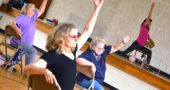 Jane Blakelock, center, stretched during a Sit Strong senior fitness class at the John Bryan Community Center this week. From the stage, fitness instructor Lynn Hardman called out and modeled the next move. Hardman, who is passionate about senior wellness, is starting a new workshop in the village focused on balance. (Photo by Megan Bachman)
