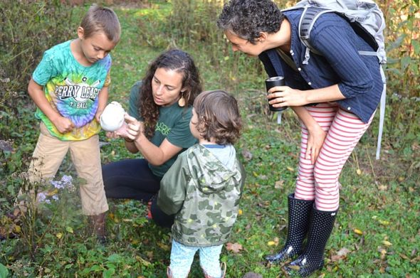 At a recent Forest Family session of the Nature Connect outdoor school, Emily Foubert looked closely at a puffball mushroom with Zander Breza, who had spotted the mushroom. Looking on are Meredith Carpe and daughter Havah, age 2. The program, Mondays from 9 to 10:30 a.m., is open to children 5 and under with an adult. Foubert, who grew up in Yellow Springs, is fulfilling her dream of opening up an outdoor school for children. Tuesday sessions for home-schooled children are also offered. (Photo by Diane Chiddister)