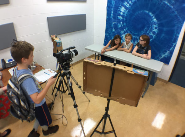 Mills Lawn student Aiden Gustafson works the camera as, from left, Stella Platt, Gabriella Kibblewhite and Tiger Collins get ready to broadcast the news on WMLS. (Photo by Carla Steiger)