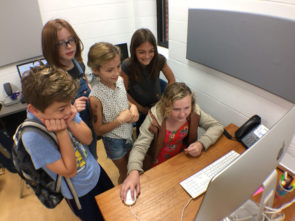Aiden Gustafson, Tiger Collins, Gabriella Kibblewhite and Stella Platt watch Cali Jones edit video on a computer. (Photo by Carla Steiger)