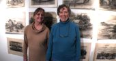 Local artists Jennifer Haack, left, and Faith Morgan, curated an exhibit highlighting the work and honoring the legacy of Dick and Nolan Miller, brothers who lived and taught in the village for more than 50 years and whose bequest started the Miller Fellows program. Some of Dick Miller's charcoal drawings of rural scenes hang behind them. (Photo by Carla Steiger)