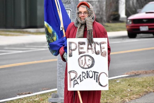 Longtime villager Peg Champney stands at the corner of Livermore Street and Xenia Avenue, part of an ongoing peace protest that has been raising awareness to passersby for more than 15 years. (Submitted photo by Luciana Lieff)
