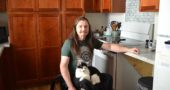 Nick Cunningham and his Japanese bobtail cat, Manny, in the fully accessible kitchen of Cunningham's new rental apartment at 511 Dayton St. The apartment, one half of a newly built duplex, is part of Forest Village Homes, an affordable, accessible rental project developed by Home, Inc. to meet local rental housing needs. (Photo by Audrey Hackett)