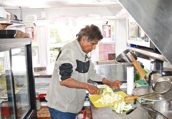 Aahar India reopened earlier this month, after closing for several months following a grease fire that severely damaged the local Indian food truck. Here, owner Akhilesh Nigam cuts cauliflower inside the new trailer he purchased and equipped, thanks in part to donations from customers and local businesses. (Photo by Audrey Hackett)