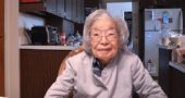 """Toshiko Asakawa sits in the kitchen of her President Street home. On the wall behind her is a drawing done by one of her grandchildren, who is now an adult. On May 9, Asakawa will celebrate her 100th birthday. (Photo by Lauren """"Chuck"""" Shows)"""