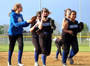 In an away game against Dayton Ponitz on Monday, April 29, Bulldog teammates Harvest Lechler, left, and Sara Zendlovist, far right, congratulate shortstop Lily Rainey, center, as she runs off the field after recording every out in the inning — including an unassisted double play on a popup. (Photo by Coach Jimmy Delong)