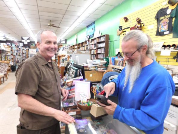 "UPS driver Rob Nangle shared a laugh with Dark Star Books staff member Frank Marcucci during a downtown delivery stop on a recent Friday. ""He's been fantastic for all the years I've worked here. I'm not sure what we'll do when he leaves,"" Marcucci said this week. (Photo by Audrey Hackett)"