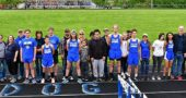 Graduating seniors on the track team pose, some with parents and siblings, after the Bulldog Invitational meet on Friday, May 3. From left: Calum Siler, Harper Mesure, Jude Meekin, Zach Lugo, Jason Lansing, Teymour Fultz, Raven Campbell, Kayla Brown and Kelli Baxter. (Photo by Kathleen Galarza)
