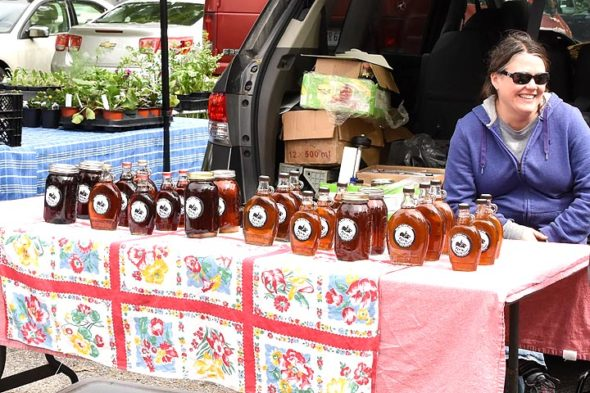 Yellow Springs Farmers Market coordinator Michele Burns sold maple syrup at her stall at the weekly market earlier this season. More recently, her Flying Mouse Farms booth has also featured greens, beets, broccoli and cauliflower. Burns sees the farmers market as a key part of the local food system.  (Photo by Luciana Lieff)