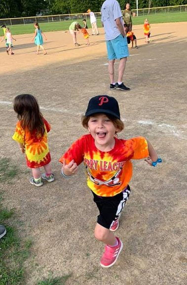 Nora Carr runs merrily off the field in full T-ball regalia at Perry League on Friday, June 21. (Submitted photo)