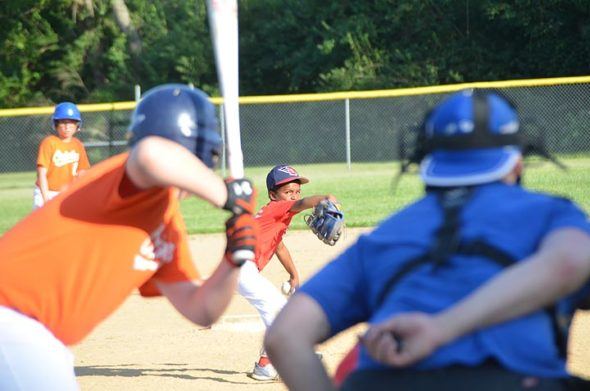 Nine year old Frank Machi, of Beavercreek, wound up and let a fierce one fly at Monday evening's rec league baseball match, pitching for the Ye Old Trail Tavern Cardinals against the Sunrise Cafe Orioles. (Photo by Matt Minde)