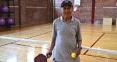 Longtime villager Tjioe Kwan, 78, came home from the National Senior Games in Albuquerque last month with a gold medal in pickleball. He plays locally at several gyms, including the Wellness Center at Antioch College, where he's pictured on a pickleball court. (Photo by Audrey Hackett)