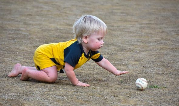 At a Perry League T-ball game earlier this month, one-year-old Ronan Triplett crawled down for a ball. (Photo by luciana Lieff )