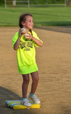 Amandine Bouquet, 5, delighted in her ball cache on Friday's Perry League T-Ball game (Photo by Luciana Lieff)